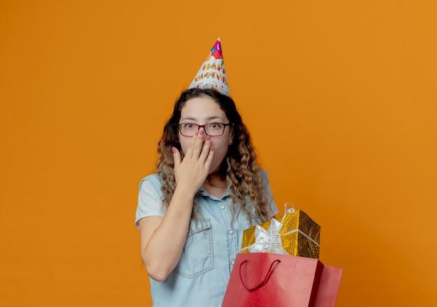 Überraschtes junges mädchen, das brille und geburtstagskappe mit geschenkboxen trägt