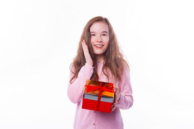 Überraschtes junges mädchen, das lächelt und eine geschenkbox über weißer wand hält