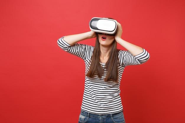 Überraschtes junges mädchen in gestreifter kleidung, virtual-reality-brille, die den mund weit offen hält, die hände auf den kopf legt, isoliert auf rotem hintergrund. menschen aufrichtige emotionen, lifestyle-konzept. kopieren sie platz.