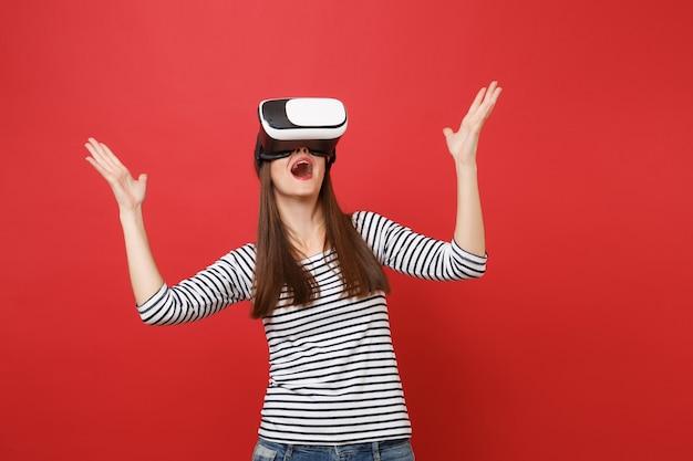 Überraschtes junges mädchen in gestreifter kleidung, virtual-reality-brille, die den mund weit offen hält und die hände einzeln auf rotem wandhintergrund ausbreitet. menschen aufrichtige emotionen lifestyle-konzept. kopieren sie platz.