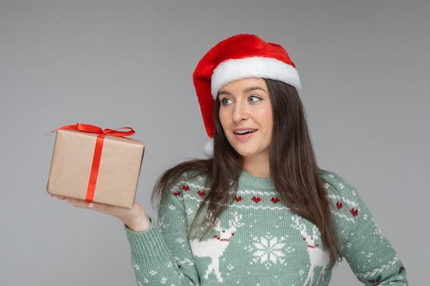 Überraschtes junges mädchen in weihnachtsmütze mit geschenk