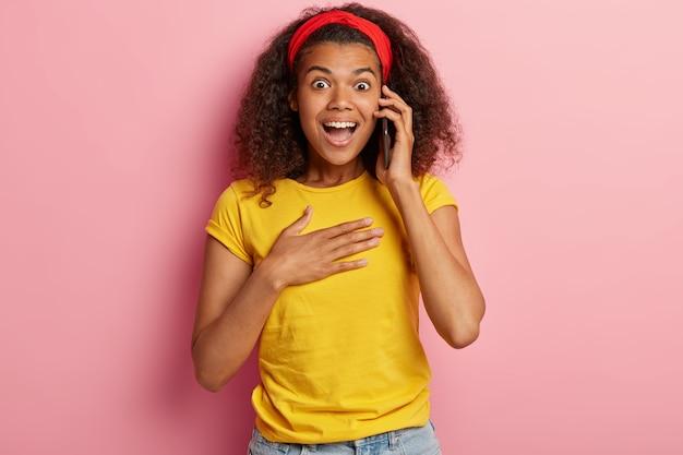 Überraschtes junges mädchen mit dem lockigen haar, das im gelben t-shirt aufwirft