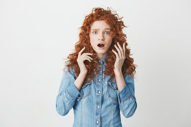 Überraschtes junges mädchen mit lockigem rotem haar mit geöffneten augen. speicherplatz kopieren.