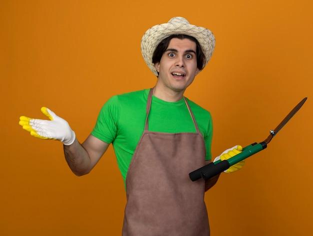 Überraschtes junges männliches gärtner in der uniform, die gartenhut mit handschuhen hält, die clipper-verbreitungshand lokalisiert auf orange halten