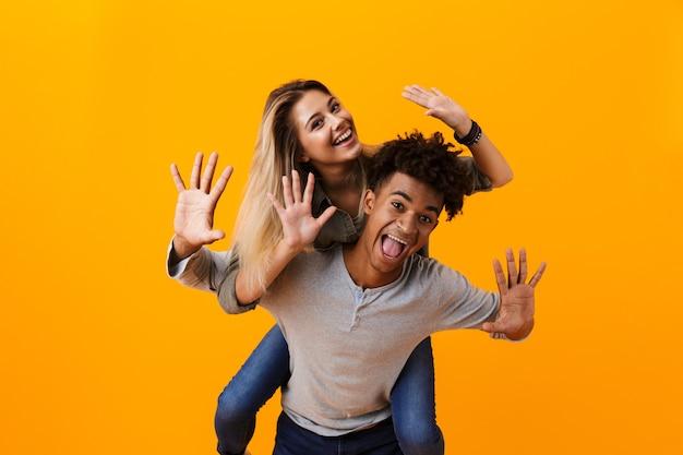 Überraschtes junges niedliches liebendes paar, das lokal über gelber wand aufwirft