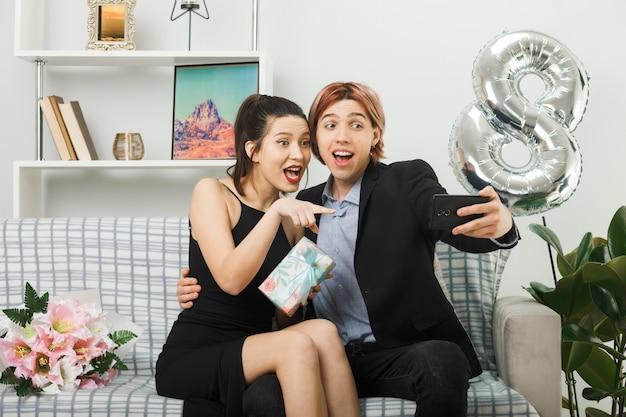 Überraschtes junges paar am glücklichen frauentag, das geschenk hält, macht ein selfie, das auf dem sofa im wohnzimmer sitzt