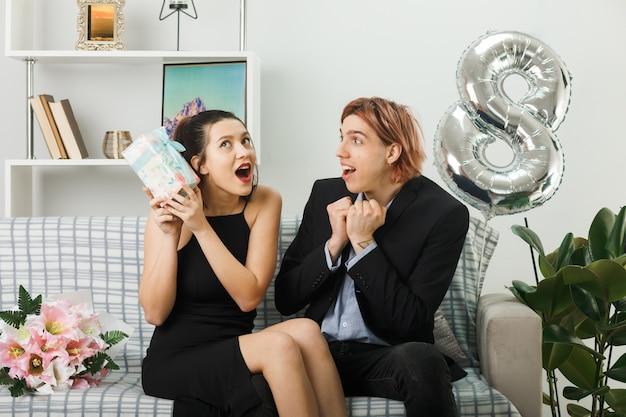 Überraschtes junges paar am glücklichen frauentag, der das geschenk auf dem sofa im wohnzimmer hält