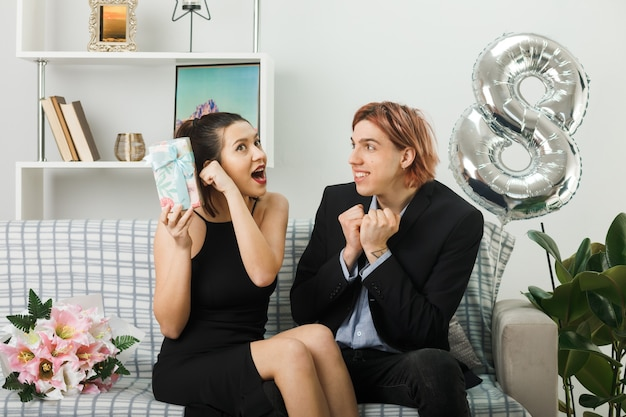 Überraschtes junges paar am glücklichen frauentag, der den anwesenden kerl hält, der eine ja-geste zeigt, die auf dem sofa im wohnzimmer sitzt?