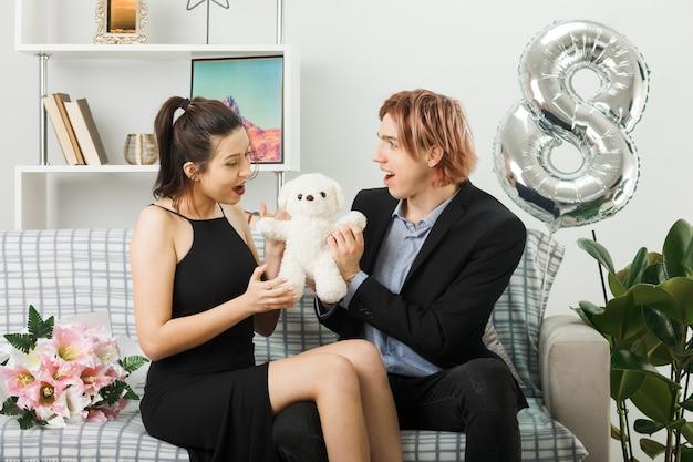 Überraschtes junges paar am glücklichen frauentag mit teddybär, der auf dem sofa im wohnzimmer sitzt