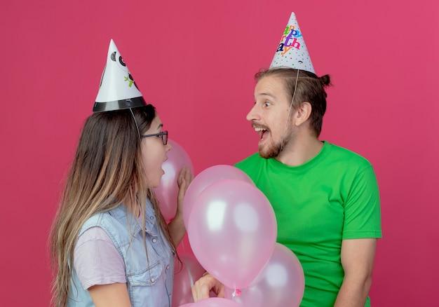 Überraschtes junges paar, das partyhut trägt, schaut einander stehend mit heliumballons lokalisiert auf rosa wand an