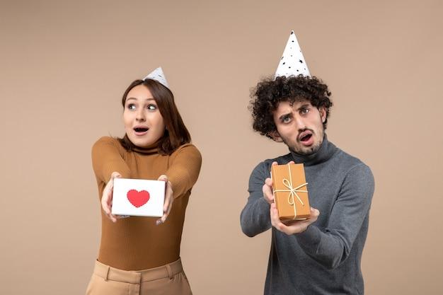 Überraschtes junges paar tragen neujahrshutposen für kameramädchen, das herz und kerl mit geschenk auf grau zeigt