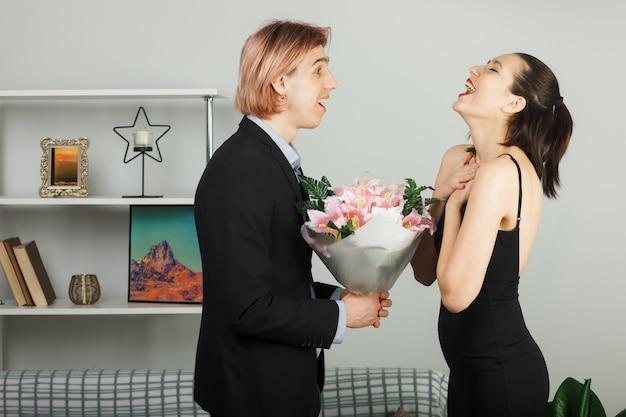 Überraschtes junges paar umarmte sich am valentinstag mit blumenstraußmädchen, die im wohnzimmer stehen