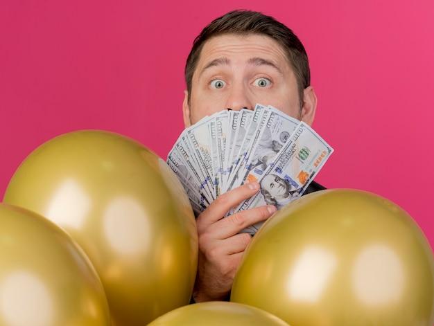 Überraschtes junges partei-kerl tragendes schwarzes hemd, das hinter luftballons bedecktem gesicht mit bargeld lokalisiert auf rosa steht