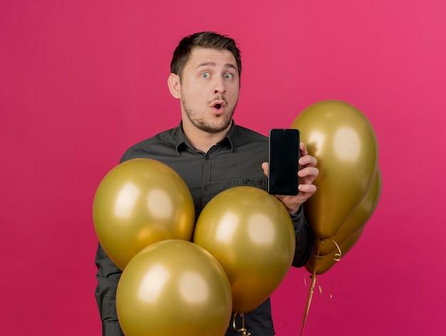 Überraschtes junges partei-kerl tragendes schwarzes hemd, das unter luftballons steht, hält telefon lokalisiert auf rosa