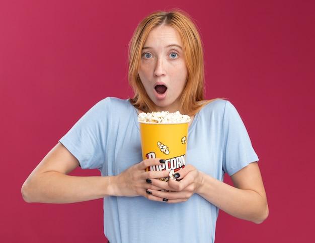 Überraschtes junges rothaariges ingwermädchen mit sommersprossen hält popcorneimer