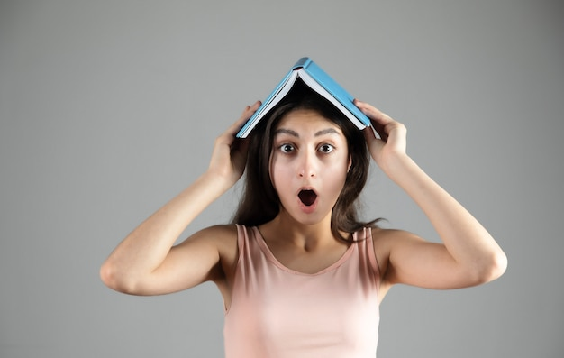 Überraschtes junges schönes frauenbuch im kopf