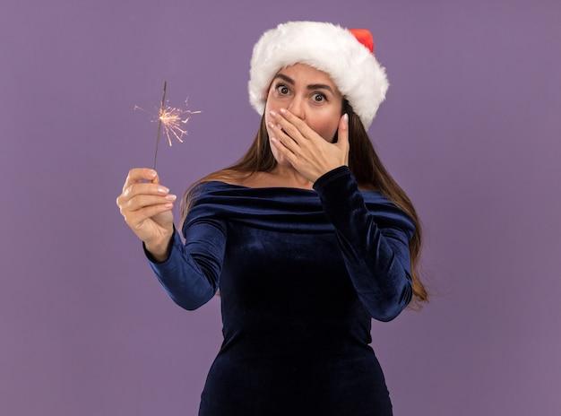 Überraschtes junges schönes mädchen, das blaues kleid und weihnachtsmütze hält wunderkerzen bedeckt mund mit hand lokalisiert auf lila hintergrund