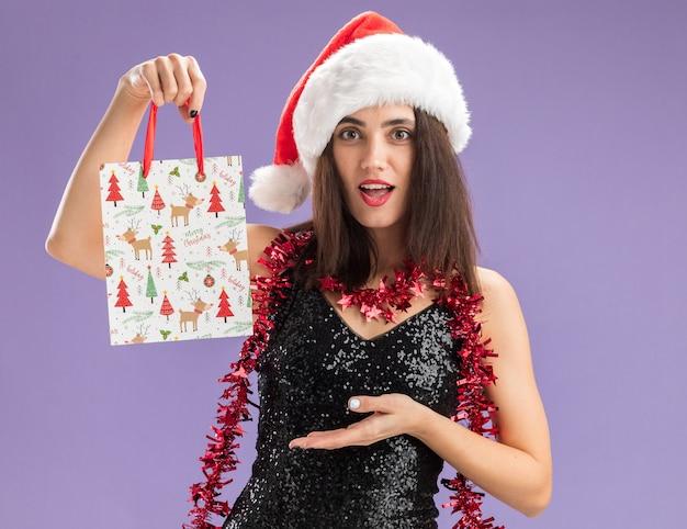 Überraschtes junges schönes mädchen, das weihnachtsmütze mit girlande am hals hält und punkte mit hand an geschenktüte lokalisiert auf lila hintergrund trägt