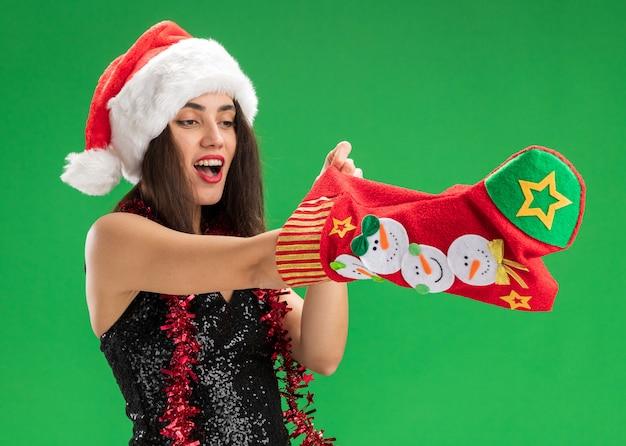 Überraschtes junges schönes mädchen, das weihnachtsmütze mit girlande am hals trägt hand in weihnachtssocke lokalisiert auf grünem hintergrund trägt