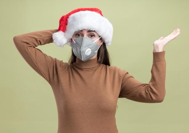 Überraschtes junges schönes mädchen, das weihnachtsmütze mit medizinischen maskenpunkten mit hand an der seite trägt hand auf kopf lokalisiert auf olivgrünem hintergrund trägt