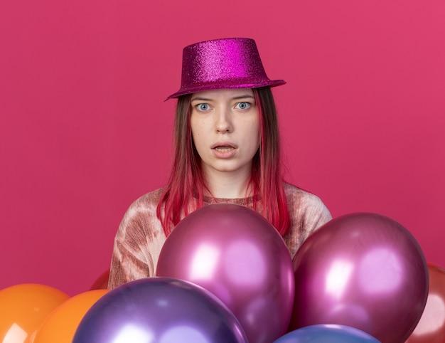 Überraschtes junges schönes mädchen mit partyhut, das hinter luftballons steht, isoliert auf rosa wand