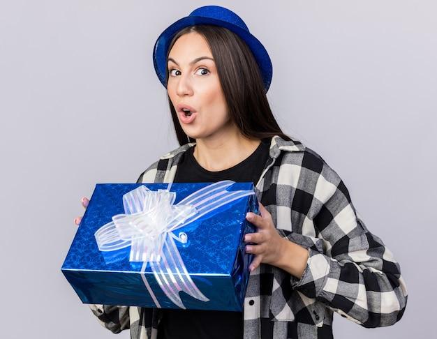 Überraschtes junges schönes mädchen mit partyhut mit geschenkbox