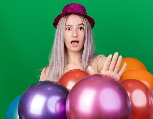 Überraschtes junges schönes mädchen mit partyhut und hosenträgern, das hinter luftballons steht und die stoppgeste einzeln auf grüner wand zeigt