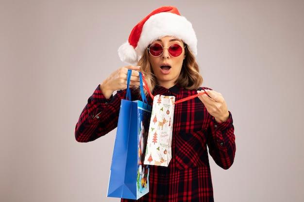 Überraschtes junges schönes mädchen mit weihnachtsmütze mit brille, das geschenktüten auf weißem hintergrund hält und betrachtet