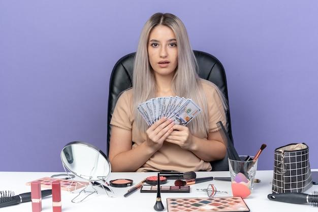 Überraschtes junges schönes mädchen sitzt am tisch mit make-up-tools, die bargeld auf blauem hintergrund halten