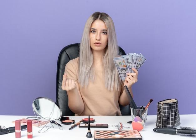 Überraschtes junges, schönes mädchen sitzt am tisch mit make-up-tools, die bargeld halten und die trinkgeldgeste einzeln auf blauem hintergrund zeigen