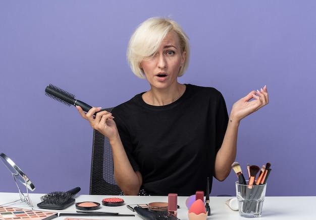Überraschtes junges schönes mädchen sitzt am tisch mit make-up-tools, die den kamm einzeln auf blauem hintergrund halten