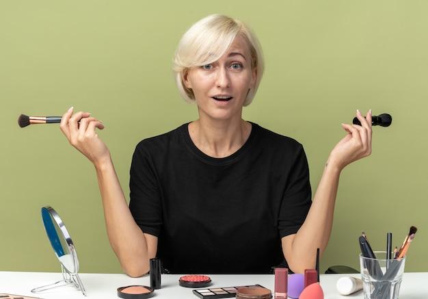 Überraschtes junges schönes mädchen sitzt am tisch mit make-up-tools, die puderpinsel halten und die hände einzeln auf olivgrünem hintergrund ausbreiten
