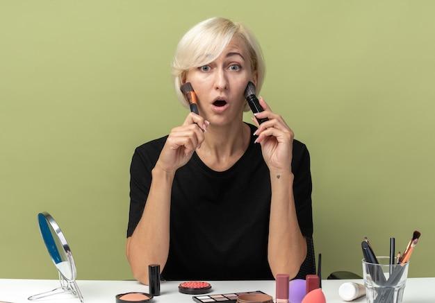 Überraschtes junges, schönes mädchen sitzt am tisch mit make-up-tools, die puderrouge einzeln auf olivgrünem hintergrund auftragen