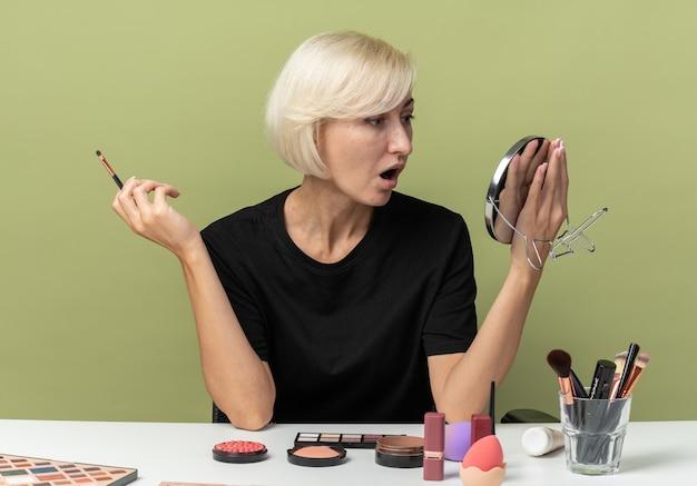 Überraschtes junges schönes mädchen sitzt am tisch mit make-up-tools und hält make-up-pinsel mit spiegel isoliert auf olivgrünem hintergrund