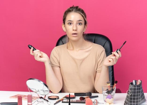 Überraschtes junges, schönes mädchen sitzt am tisch mit make-up-werkzeugen, die puderrötungen halten, die hände einzeln auf rosafarbenem hintergrund verteilen