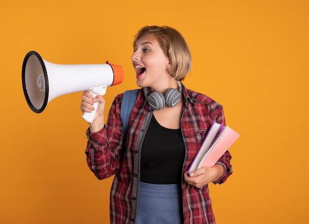 Überraschtes junges slawisches studentenmädchen mit kopfhörern, das rucksack trägt, hält buch und notizbuch schreit in den lautsprecher
