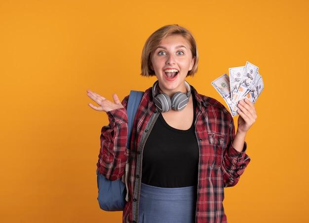 Überraschtes junges slawisches studentenmädchen mit kopfhörern, das rucksack trägt, hält die hand offen und hält geld