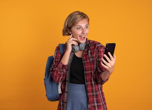 Überraschtes junges slawisches studentenmädchen mit kopfhörern, das rucksack trägt, legt die hand auf das gesicht, das telefon hält und betrachtet