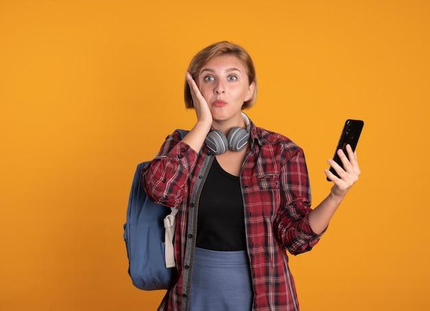 Überraschtes junges slawisches studentenmädchen mit kopfhörern, das rucksack trägt, legt hand auf gesicht hält telefon