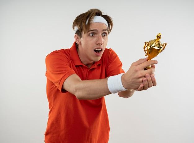 Überraschtes junges sportliches kerltragen-stirnband mit armband mit handgelenk gewickelt mit verband, der siegerbecher an der seite lokalisiert auf weißer wand heraushält