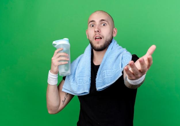 Überraschtes junges sportliches manntragen armband, das wasserflasche mit handtuch auf schulter hält und hand lokalisiert auf grüner wand hält