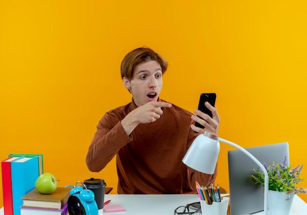 Überraschtes junges studentenjungen, das am schreibtisch mit den schulwerkzeugen hält und auf telefon auf gelb zeigt