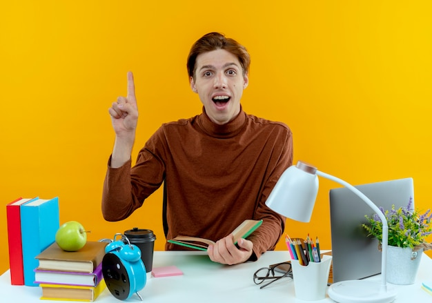 Überraschtes junges studentenjungen, das am schreibtisch mit schulwerkzeugen sitzt, die buch halten und oben auf gelb zeigen
