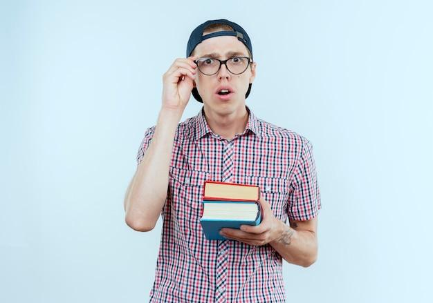 Überraschtes junges studentenjungen, das rückentasche und brille und kappe hält bücher hält und hand auf brille lokalisiert auf weißer wand setzt