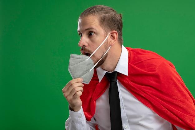 Überraschtes junges superhelden-mann, das medizinische maske und krawatte trägt, die seite betrachtet und ergriffene medizinische maske lokalisiert auf grünem hintergrund