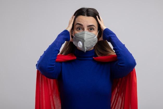Überraschtes junges superheldenmädchen, das medizinische maske trägt, ergriff kopf lokalisiert auf weiß