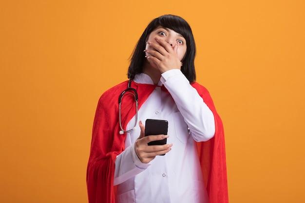 Überraschtes junges superheldenmädchen, das stethoskop mit medizinischem gewand und umhang hält, der telefon bedeckten mund mit hand hält