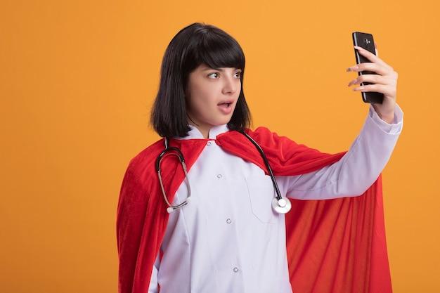 Überraschtes junges superheldenmädchen, das stethoskop mit medizinischem gewand und umhang hält, der telefon hält und betrachtet