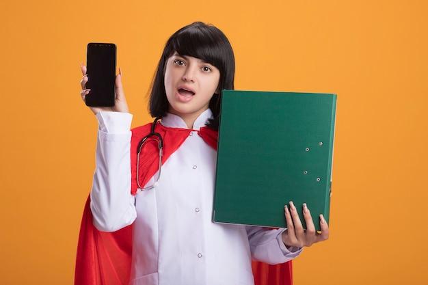 Überraschtes junges superheldenmädchen, das stethoskop mit medizinischem gewand und umhang hält telefon mit ordner trägt