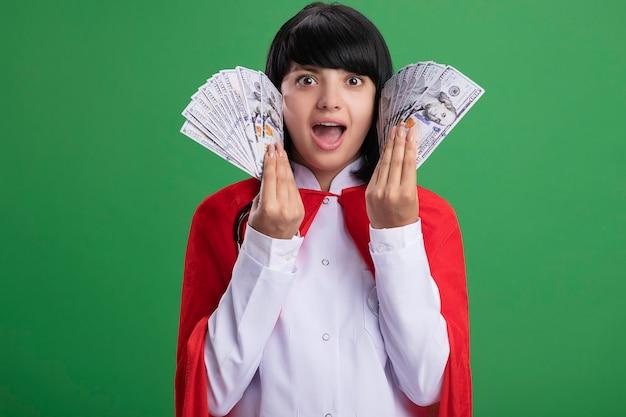 Überraschtes junges superheldenmädchen, das stethoskop mit medizinischem gewand und umhang trägt, der bargeld um gesicht lokalisiert auf grüner wand hält